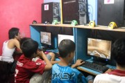 Indonesian kids playing online computer games at an internet cafe in Indonesia.