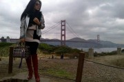 Indonesian singer Syahrini in San Francisco with Golden Gate Bridge in background.