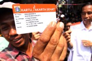 Indonesian man holding up Jakarta Health Card (KJS) launched by Govornor Jokowi.
